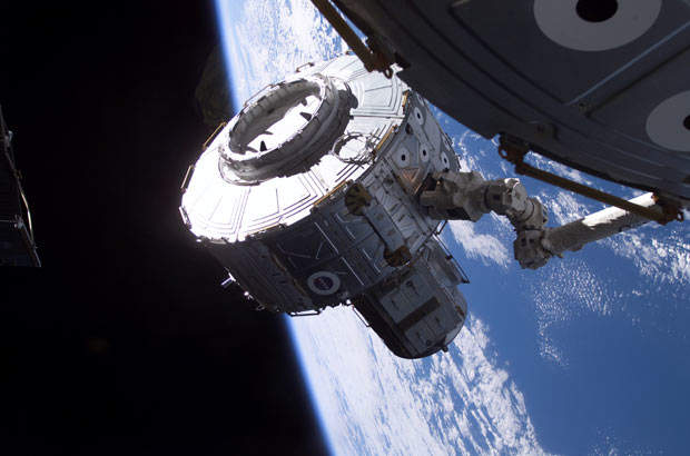 Quest airlock in the process of being installed onto the starboard side of Unity Node 1 using the Space Station Remote Manipulator System (SSRMS).
