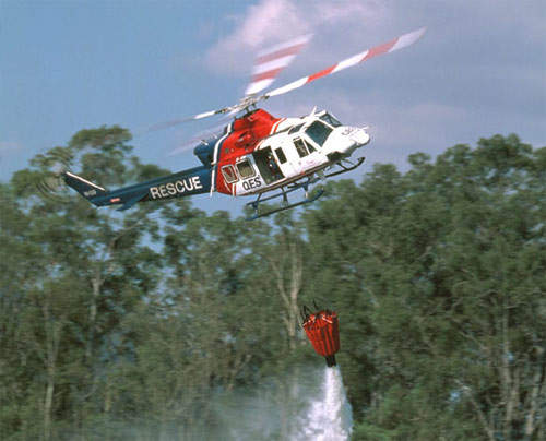 The 412 on a fire-fighting mission using a 'bambi bucket' to drop water.