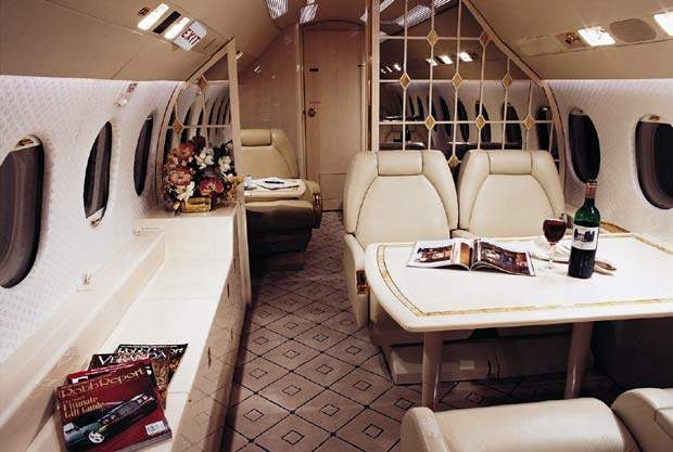 The interior of the Dassault Falcon 900C business jet is fitted with functional tables for work or pleasure.