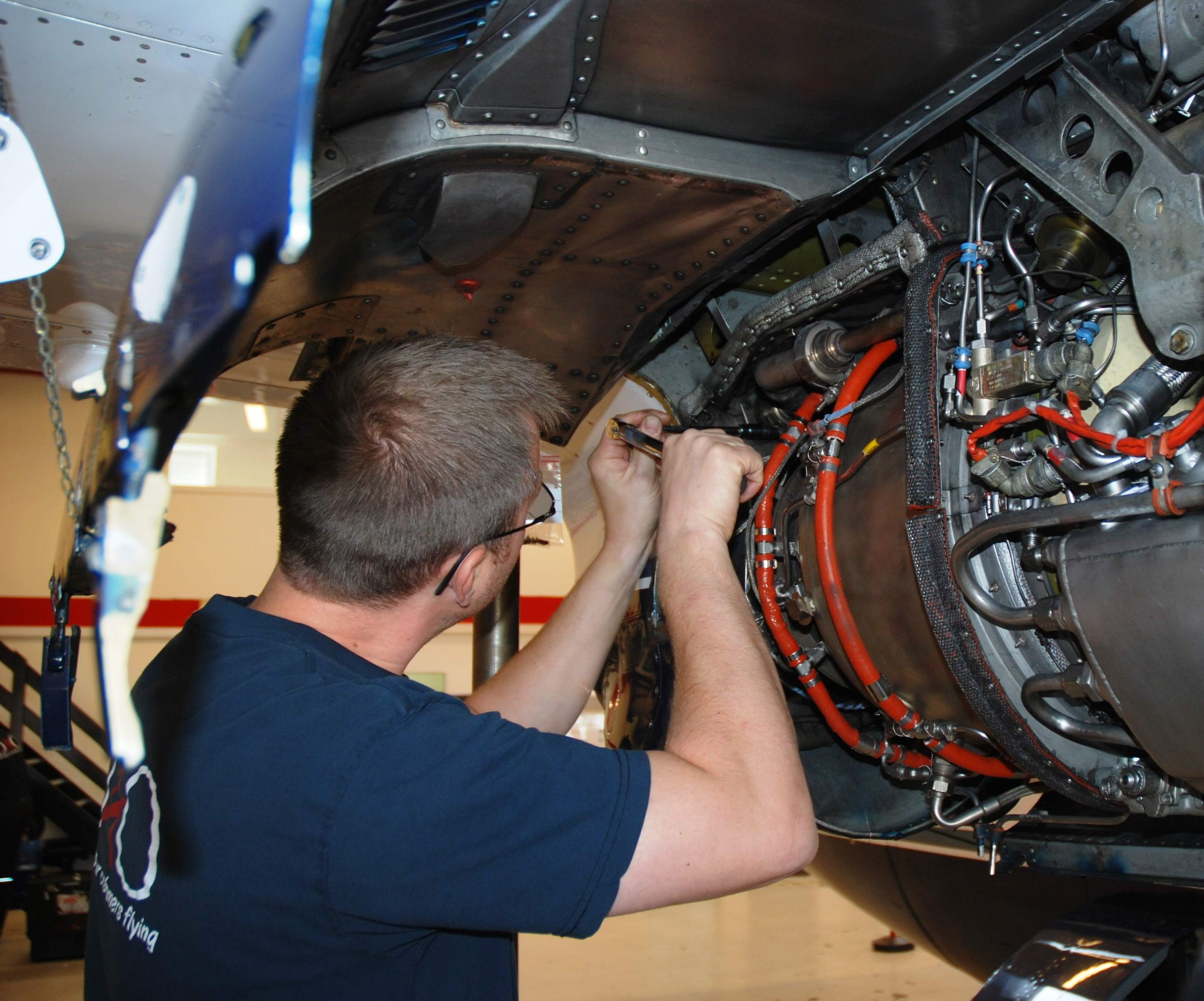 A man fixing an aircraft engine