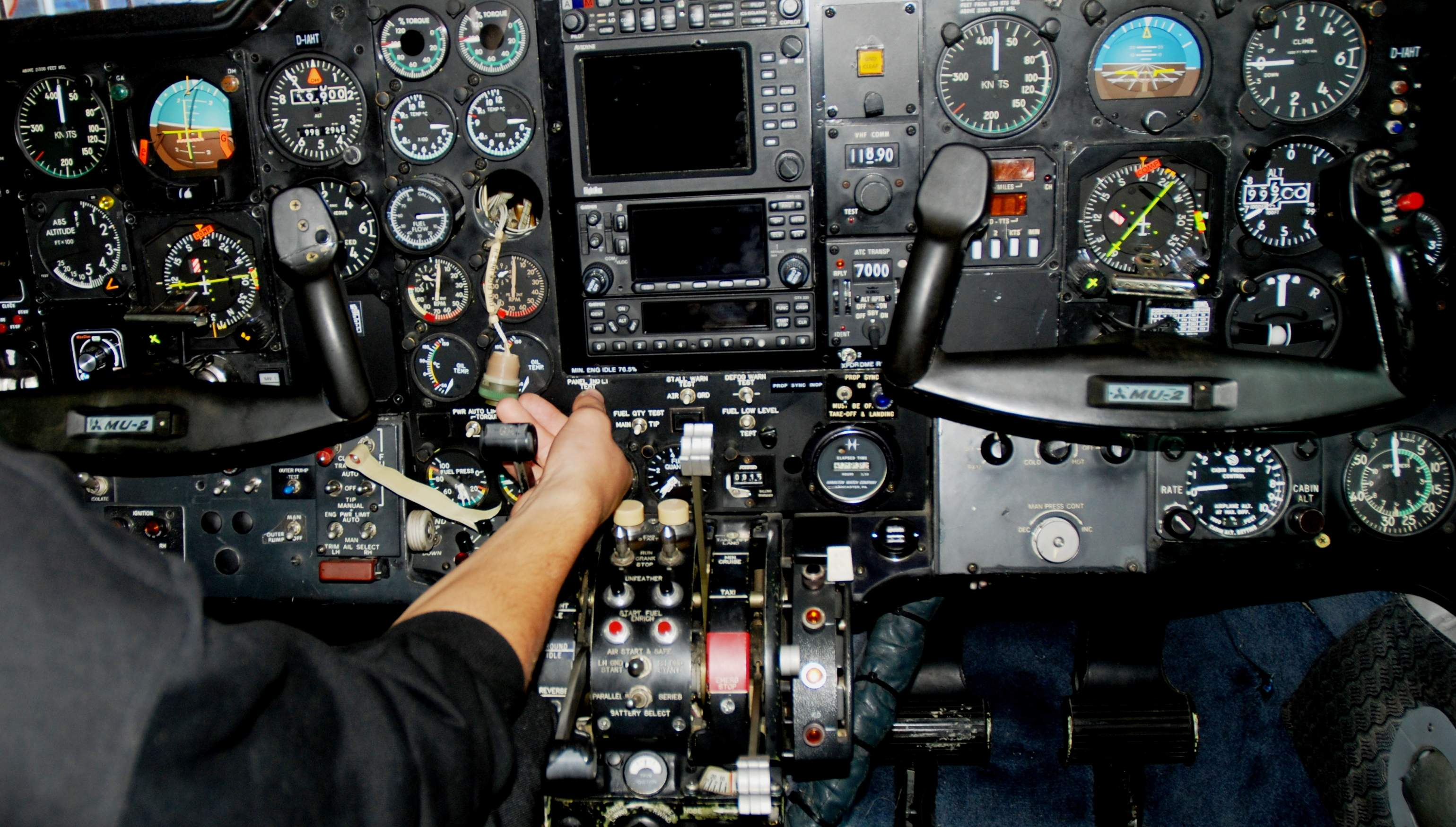 The control panel of an aircraft with a man's hand